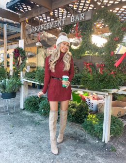 blogger in red dress holding starbucks in a christmas tree farm